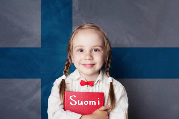 學習芬蘭文。在芬蘭國旗背景的聰明的兒童女孩 - 芬蘭 個照片及圖片檔