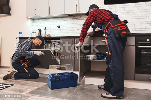 Learning from the best. Two men technician senior and young are sitting near dishwasher with screwdriver in kitchen with instruments Senior man teaches young one