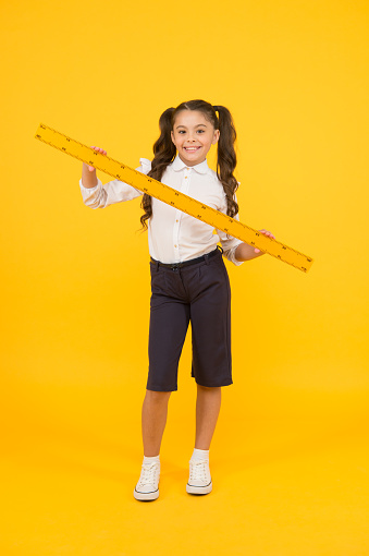 Learning geometry at school. Small school child holding measuring device on yellow background. Little girl preparing long wooden ruler for school lesson. Keep measuring and back to school.