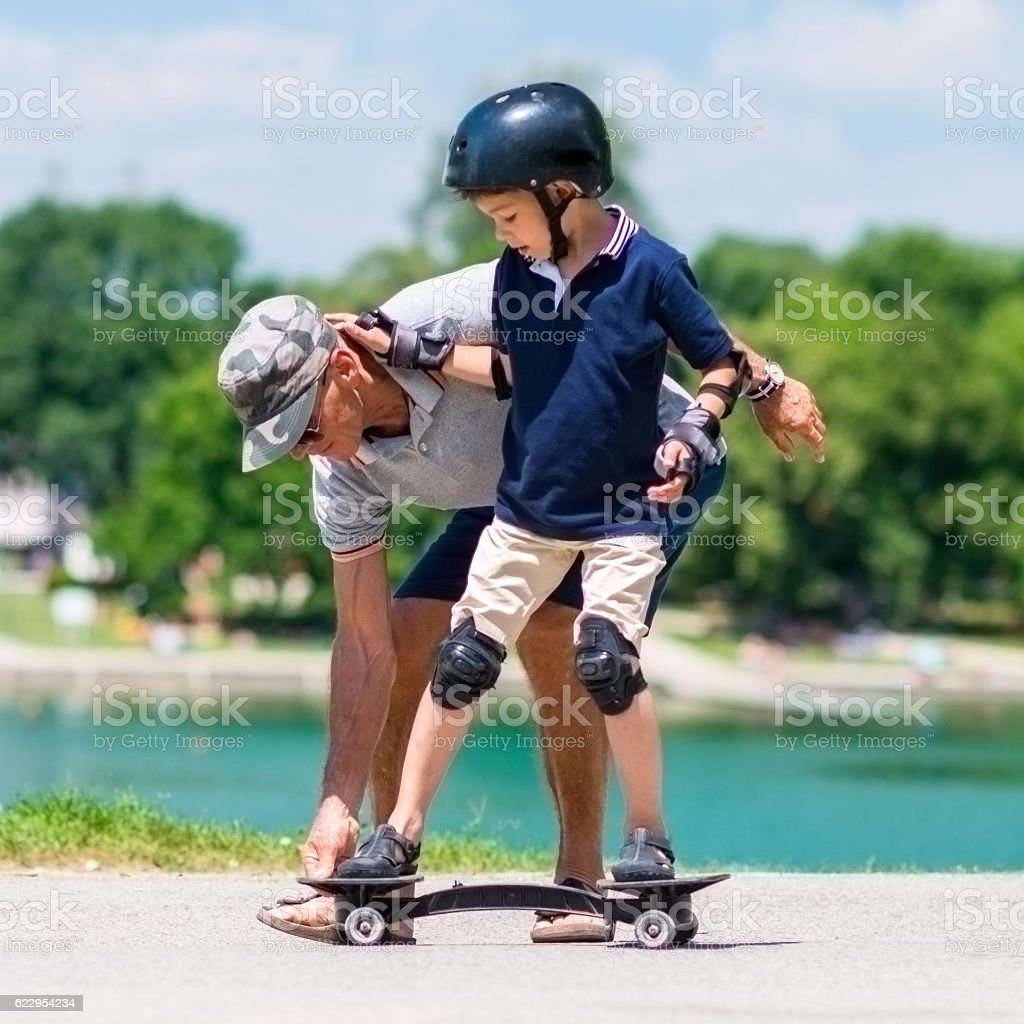 Learning how to ride a snakeboard by the lake - foto de acervo