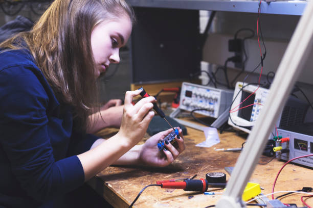 Learning how to solder at a University courses Female STEM student working in her University's electronics lab to operate a small circuit board. soldering iron stock pictures, royalty-free photos & images