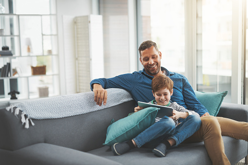 Shot of a cheerful little boy browsing on a digital tablet while lying on his father's lap at home during the day