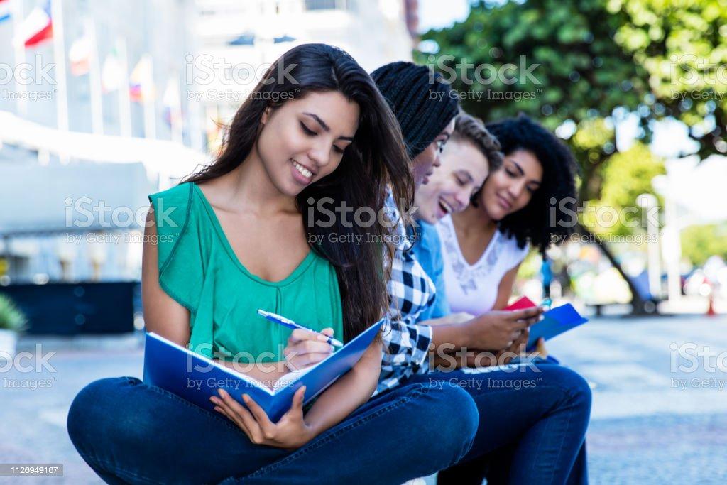 Aprendizaje de estudiante femenino de América Latina con el grupo de estudiantes internacionales al aire libre en el verano en la ciudad - foto de stock