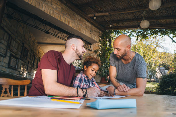 Learning math together! Male couple learning their daughter math gay person stock pictures, royalty-free photos & images