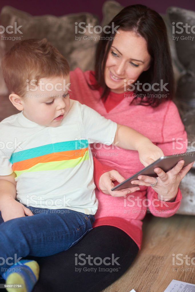 mother and toddler using digital tablet at home to play games, read...