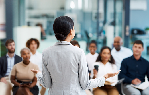 Rearview shot of an unrecognizable businesswoman giving a presentation in the office boardroom
