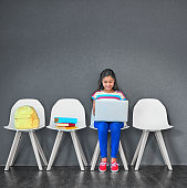 Studio shot of a young girl sitting on a chair and using a laptop against a gray background