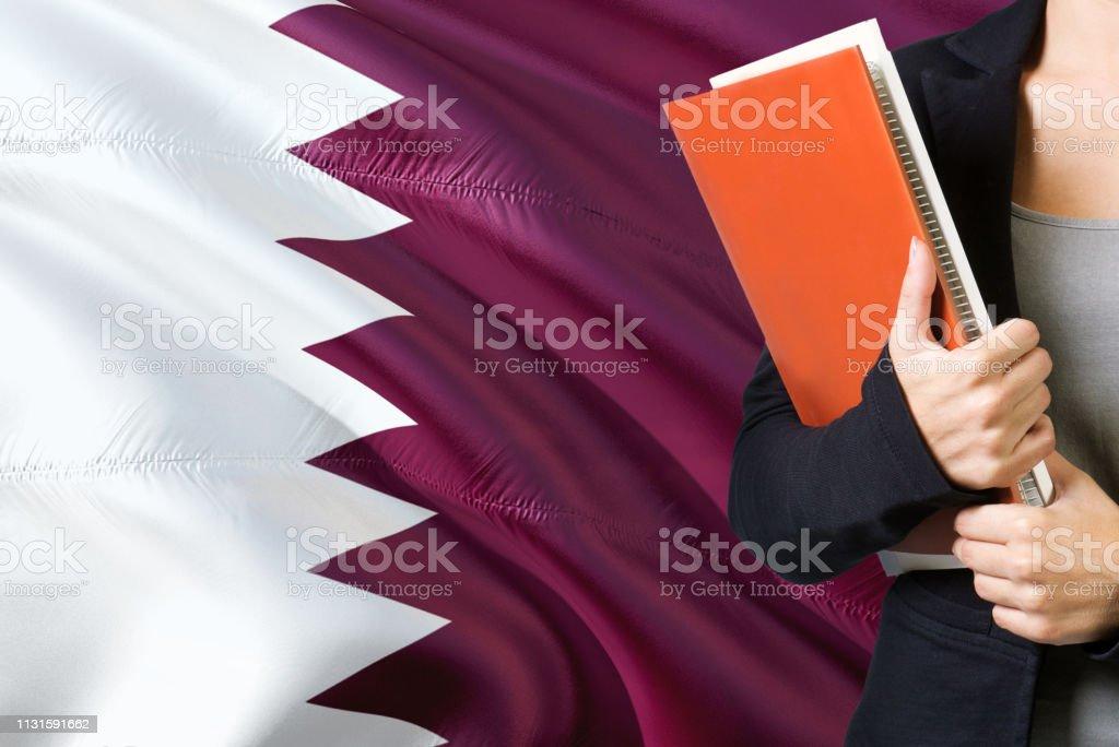 Aprendiendo el concepto del lenguaje qatarí. Mujer joven de pie con la bandera de Qatar en el fondo. Profesor sosteniendo libros, cubierta anaranjada del libro en blanco. - foto de stock