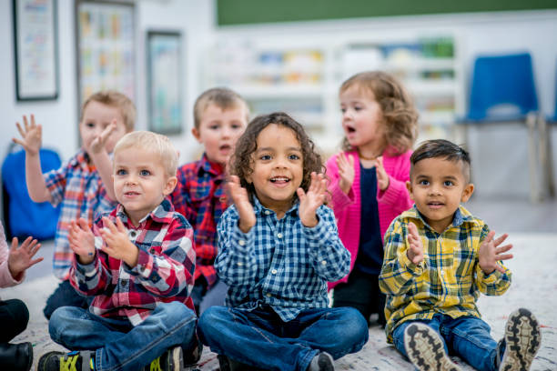 Learning Rhythm A multi-ethnic group of young children are at a preschool. They are sitting on the carpet and clapping along to a music CD. preschool age stock pictures, royalty-free photos & images