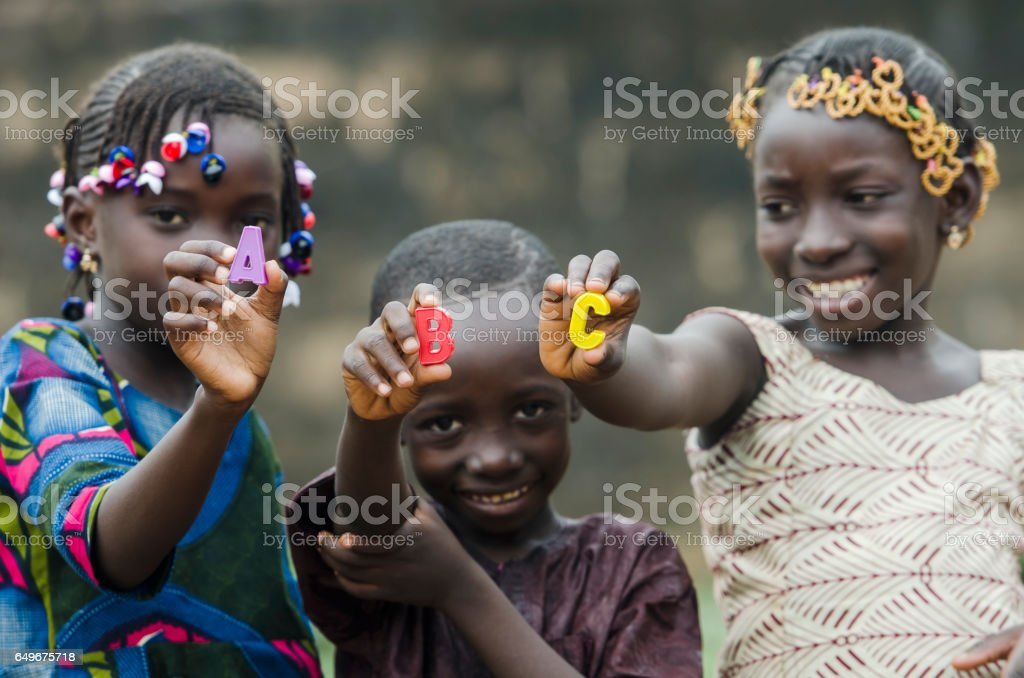 Learning the Alphabet - Beautiful African Portrait of Children Smiling Outdoors stock photo