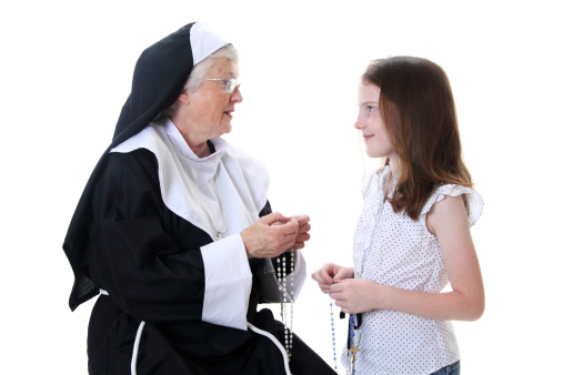 Mature nun teaching a  little girl to pray the rosary