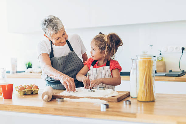 learning to make cookies like grandma - granddaughter and grandmother stock photos and pictures