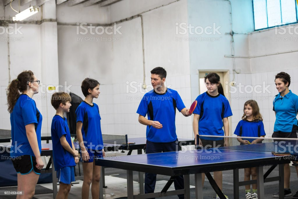 Group of table tennis players talking during class.
