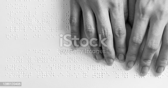 Fingers of a blind person reading some braille text touching the relief.