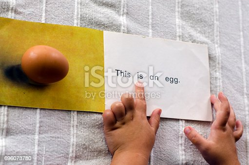 A hands of a preschooler learning to read the English word, Egg.