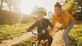 Photo of a young boy who is learning to ride a bicycle with a little help from his mother; wide photo dimensions