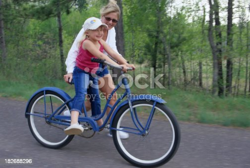 Mother takes her daughter out on a big old bicycle on a country road