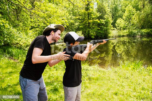 A man teaching a pre-adolescent boy how to shoot a rifle safely.