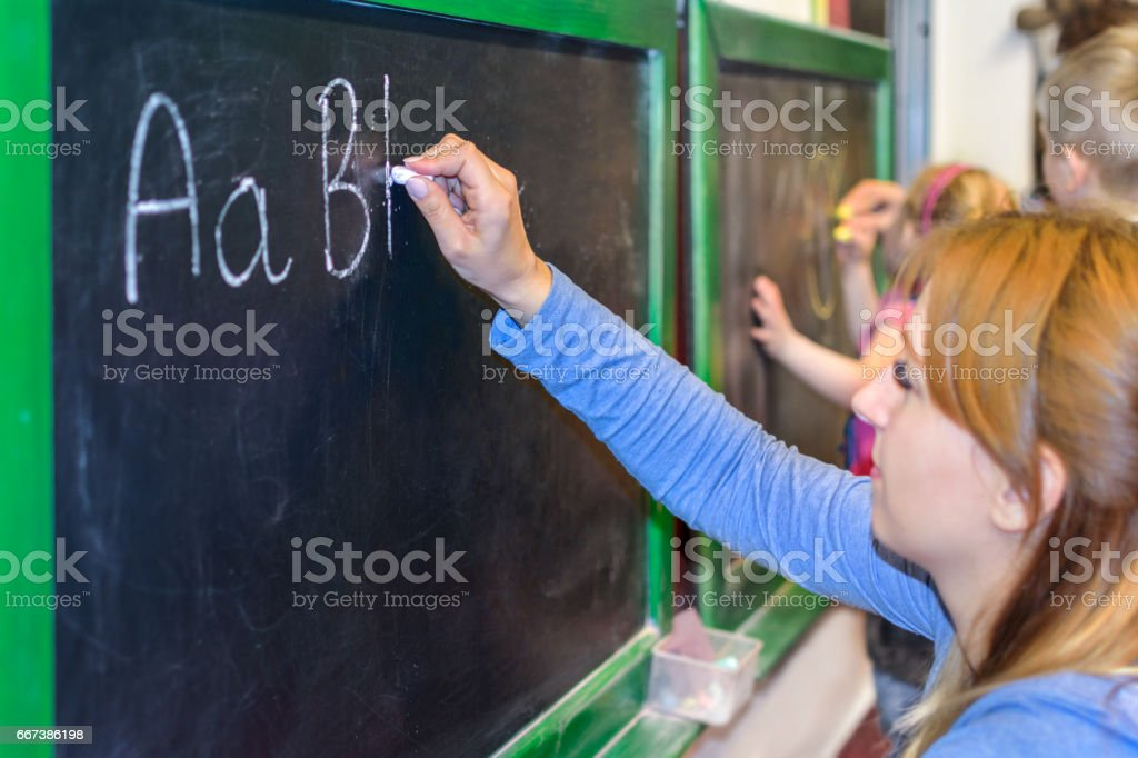 Learning to write ABC on the blackboard stock photo