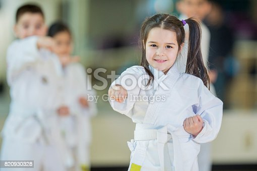 A multi-ethnic group of children are indoors at a Taekwondo academy. They are wearing martial arts clothing. A Caucasian girl is practicing her punching while smiling at the camera.