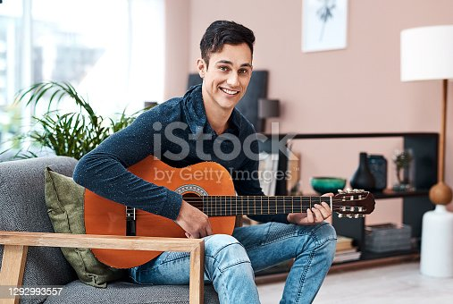 Portrait of a young man playing a guitar at home