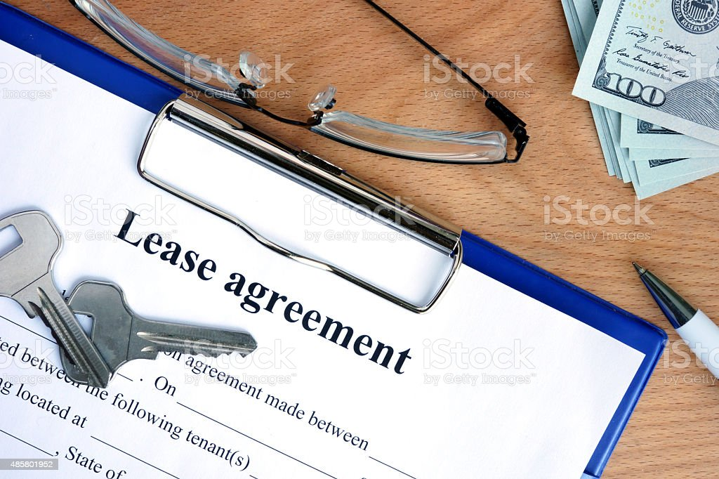 Lease agreement document with money on a wood background stock photo