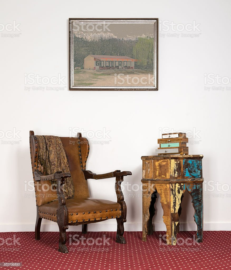 Leather armchair, vintage round table and painting on red carpet stock photo