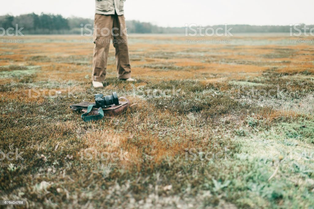 Leather bag with gloves and camera lying in field. Legs of man in background. stock photo