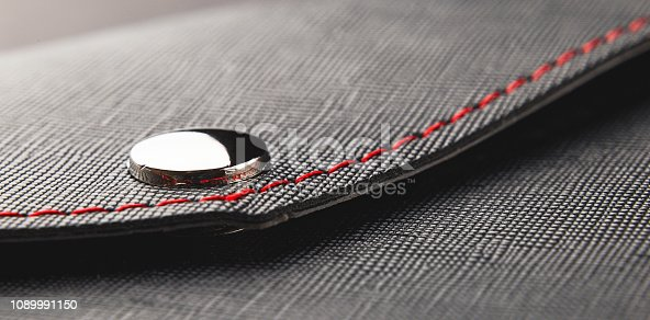 1128272390 istock photo Leather black close up, rivet and red thread business style background 1089991150