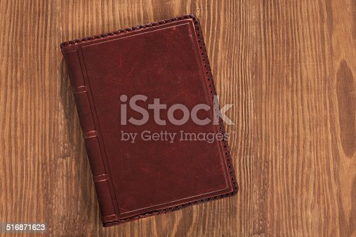 istock leather book on wooden board 516871623