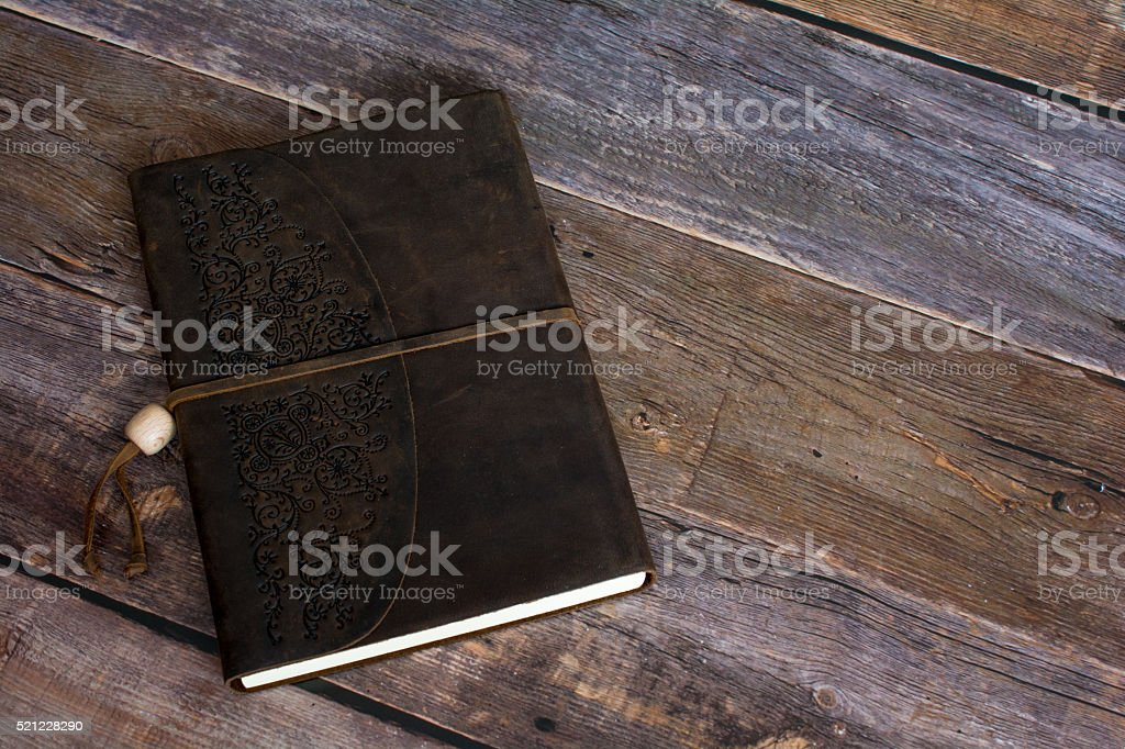 Leather Bound Journal Book on a Old Barn Board Floor stock photo
