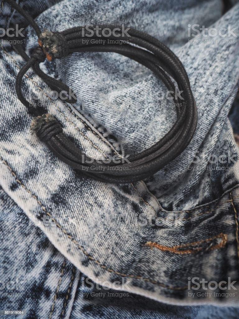 Leather bracelet on jeans stock photo