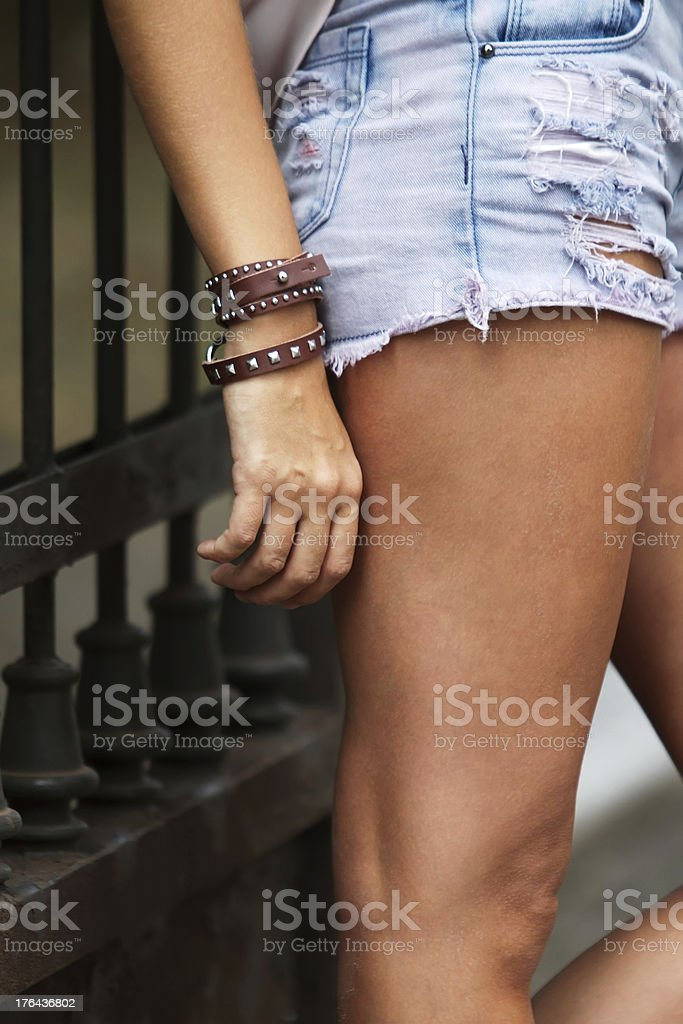 Leather bracelet with spikes and torn jeans royalty-free stock photo