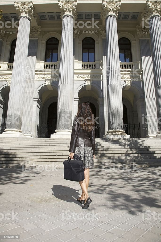 leather businesswoman in front of columns royalty-free stock photo