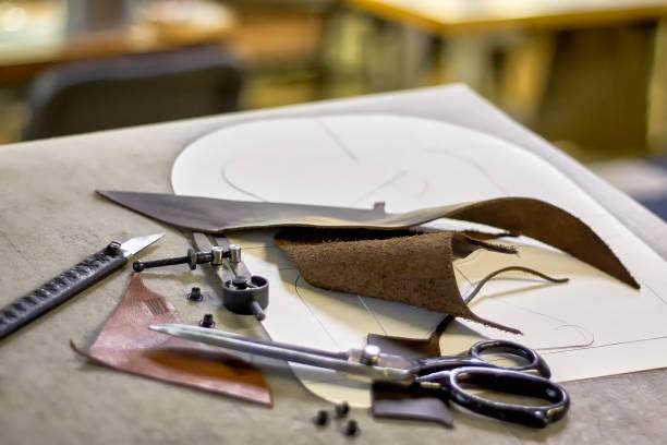 leder-bastelwerkzeug und schablonen auf der werkbank. - diy leder stock-fotos und bilder