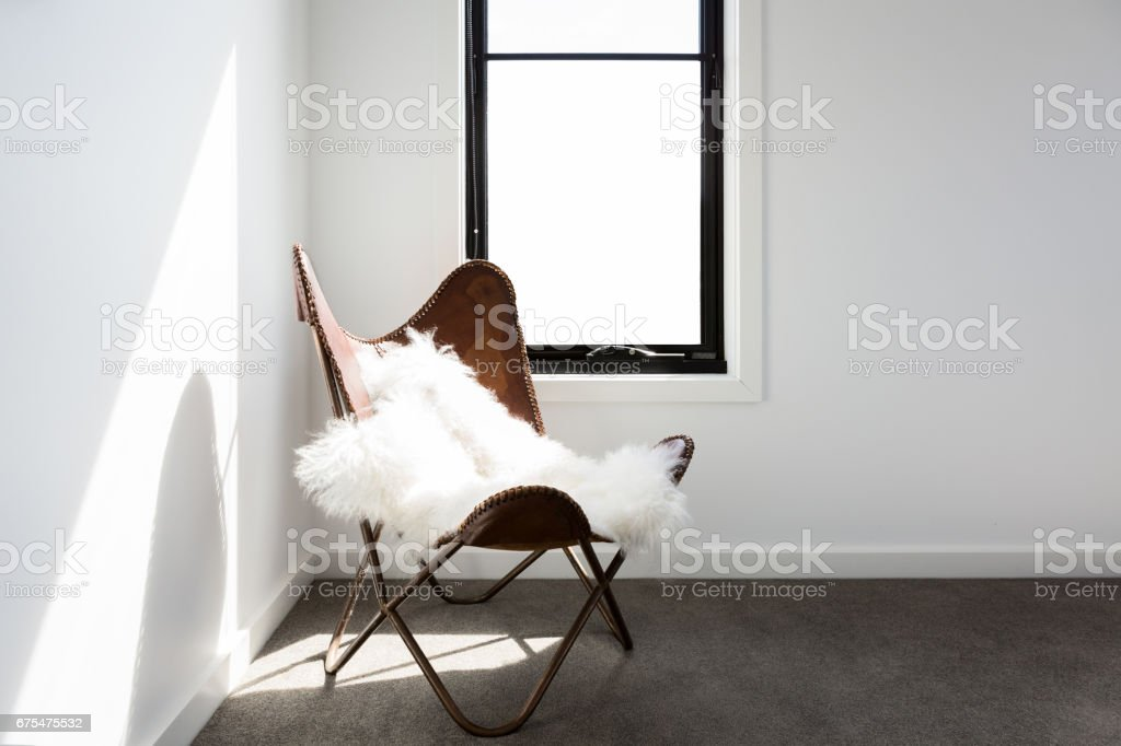 Leather occasional chair with sheepskin stock photo