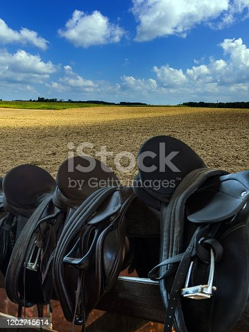 Leather Saddles equestrian with stirrups on fence, agricultural land field plowing, blue sky clouds.