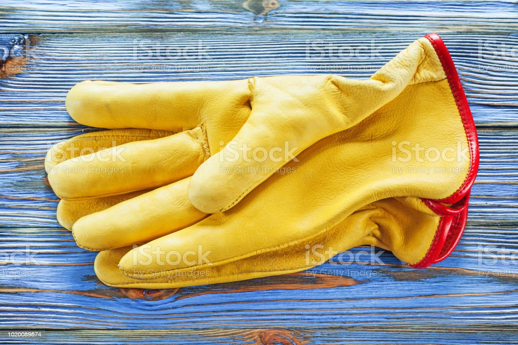 Leather safety gloves on vintage wooden board.