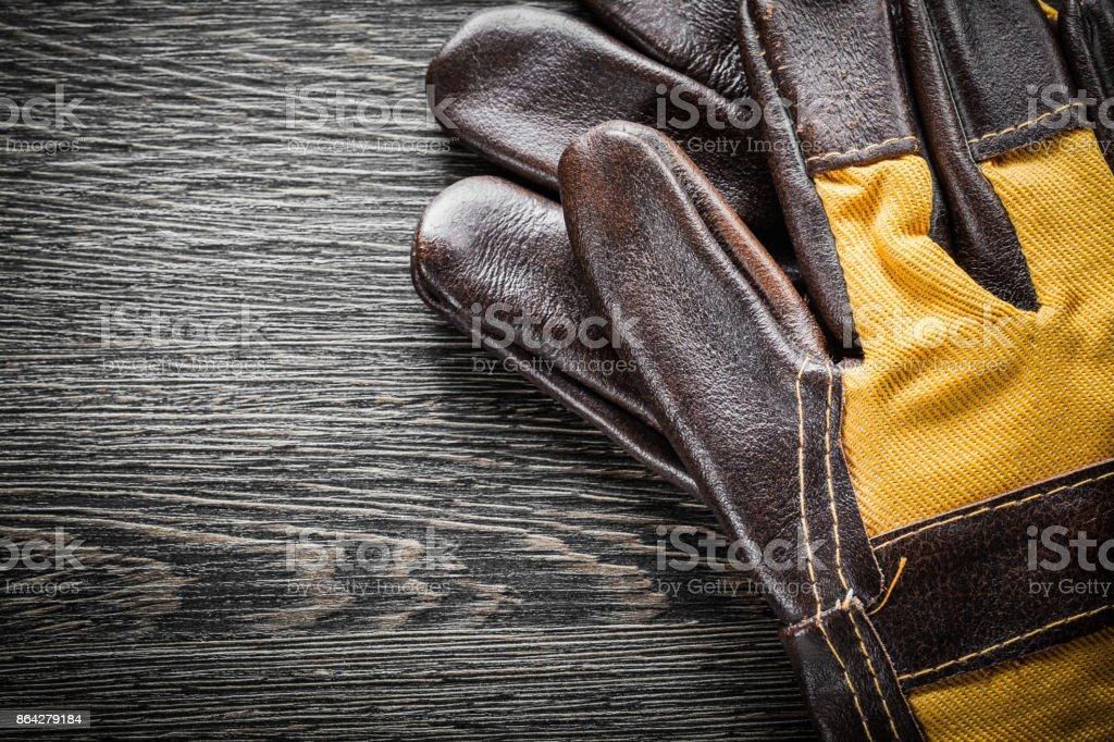 Leather safety gloves on wooden board royalty-free stock photo