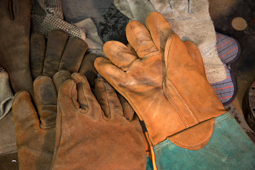 Various styles of protective work gloves laid out on work bench.