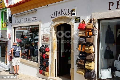 Tourists standing outside a leather goods shop in the old town with tourists enjoying the setting, Albufeira, Portugal, Europe.