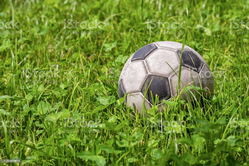 Old leather soccer ball on green grass with copy space, football...