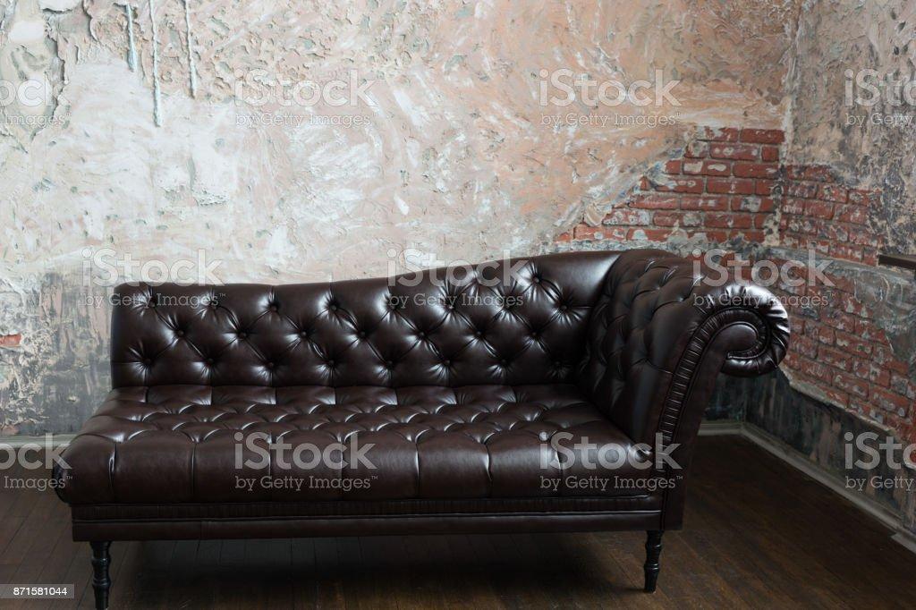 Leerbank in de engelse stijl in de kamer met oude bakstenen muren