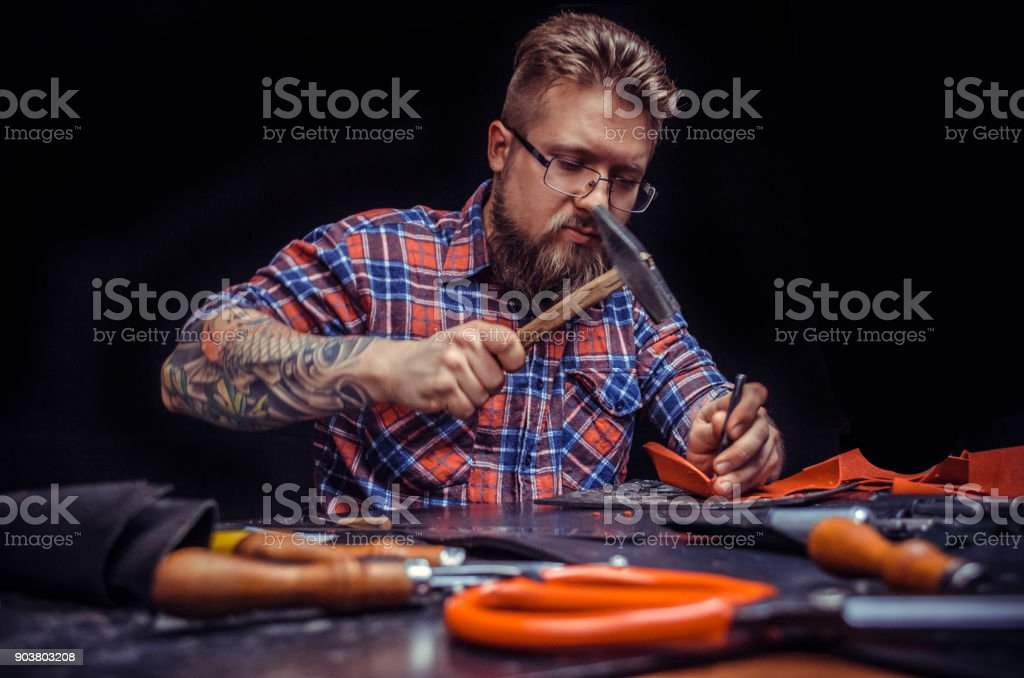 Leather Tanner cuts out leather goods in the work area stock photo