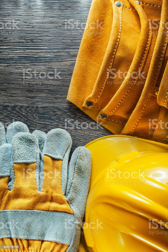Leather tool belt building helmet pair of safety gloves on woode stock photo