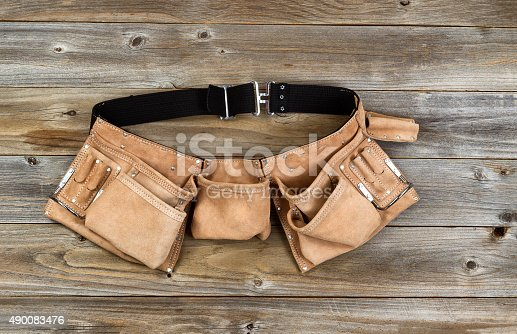 istock Leather tool belt on rustic wooden boards 490083476