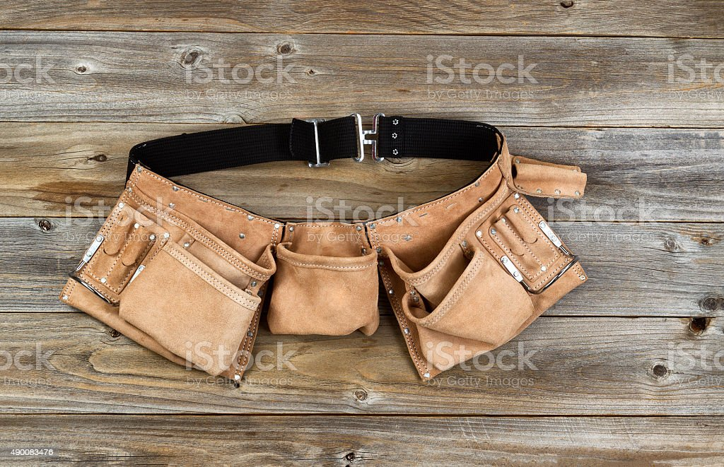 Leather tool belt on rustic wooden boards stock photo