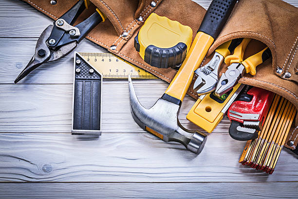 leather tool belt with construction tooling on wooden board main - tool belt stock photos and pictures