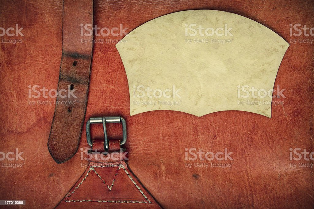 Leather vintage background with a buckle and paper frame royalty-free stock photo