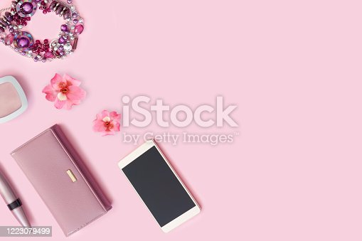 847905020 istock photo Leather wallet,  bracelet, lipstick and new smartphone on bright rose background. 1223079499